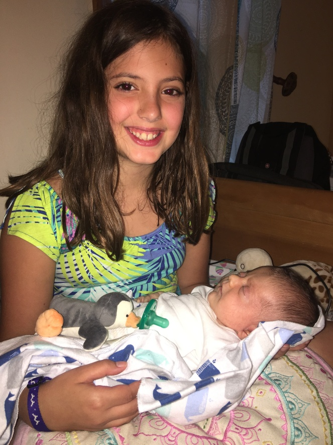 Big sister Charlie so happy to hold her baby
